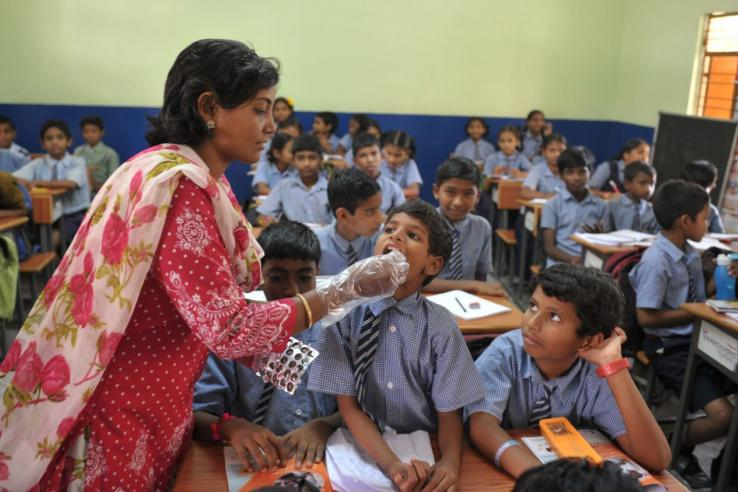 A teacher gives a deworming tablet to a student during National Deworming Day at a high school in Hyderabad, India in 2017.