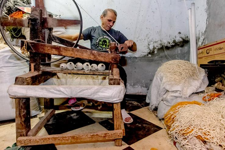 Man using spinning wheel next to piles of thread
