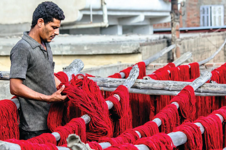 man holding red thread