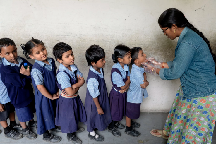 children in line to take deworming tablets in India