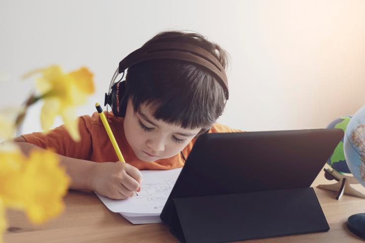 A young boy wearing headphones writes on a piece of paper in front of a laptop