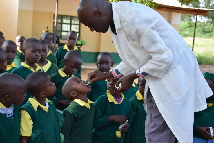 Children taking deworming pills in Kenya