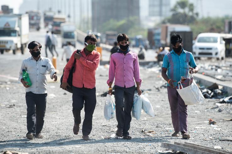 Four laborers wearing masks and walking in India during the lockdown