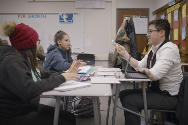 Two high school students sit at desks with their tutor for personalized instruction