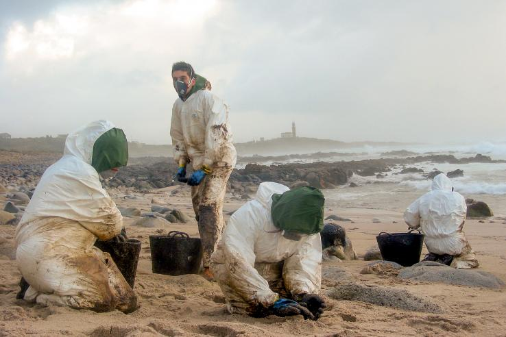 Four people wearing white hazard suits clean up oil on a beach