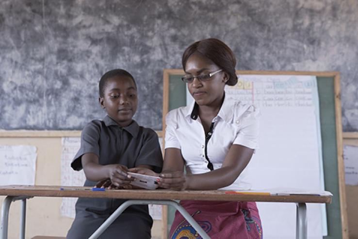 Women sitting at a desk with school child. They look like they are learning or studying together.