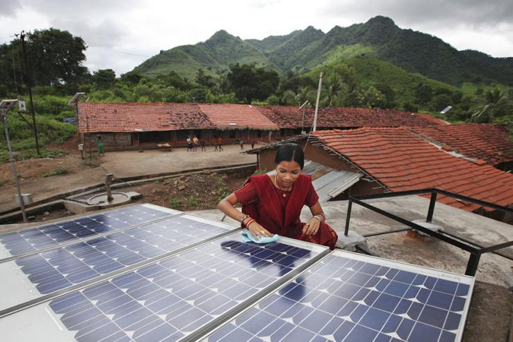 A woman cleans a solar panel.
