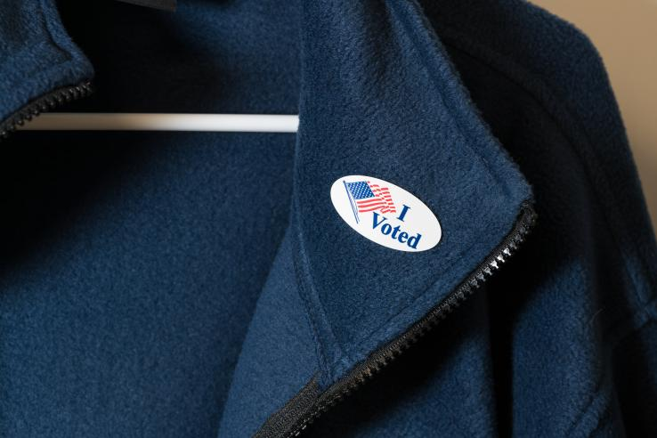 "An ""I voted"" sticker with an American flag on a blue jacket"