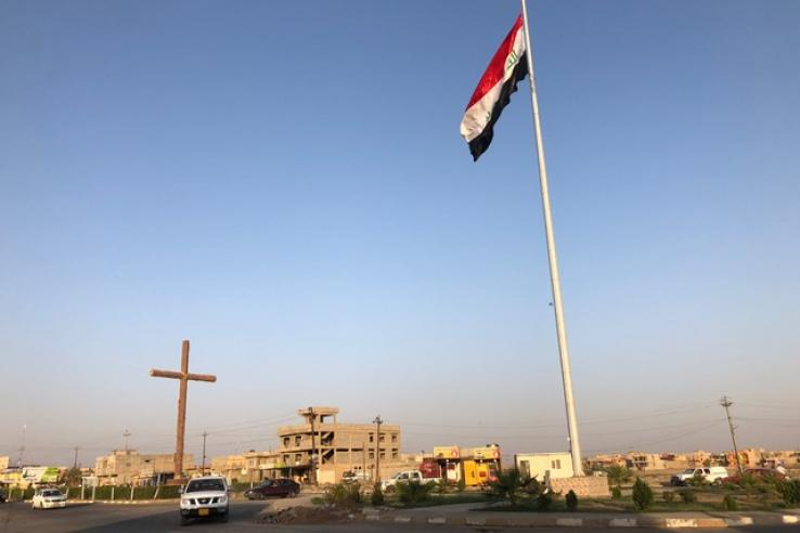 A car drives by a cross and Iraq's flag