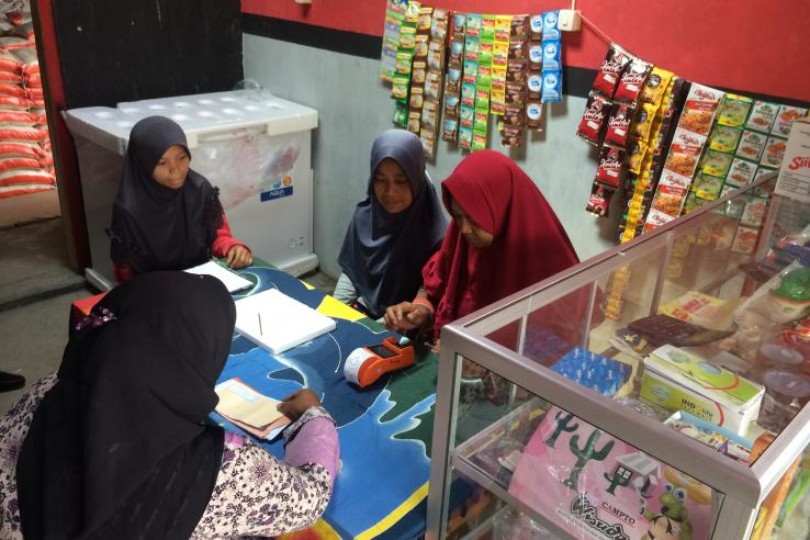 Four women group around a counter at a small shop. One woman is performing a transaction on a digital card reader.