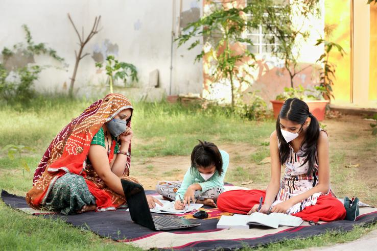 A women wearing a face mask sits outside with two children, also wearing face masks.