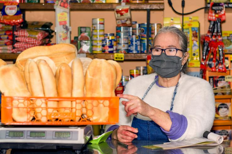 A woman wearing a mask weighs bread in a store