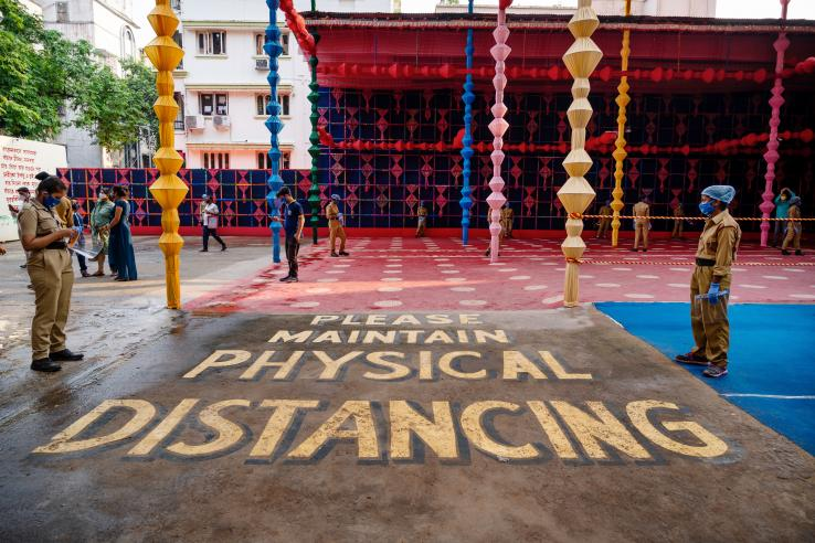"people gathered to celebrate a festival in Kolkata with a huge sign which says ""please maintain physical distancing"" painted on the ground"