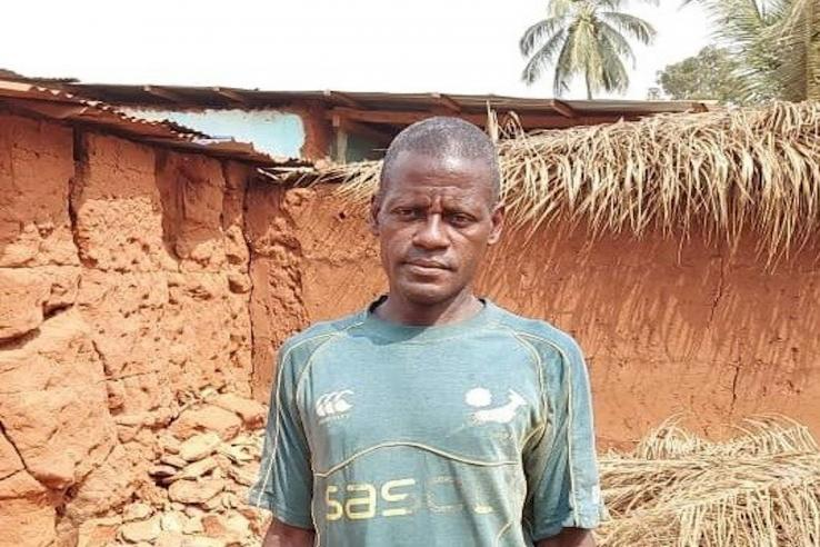 Farmer in a blue T-shirt looking int the camera in front of a brown wall