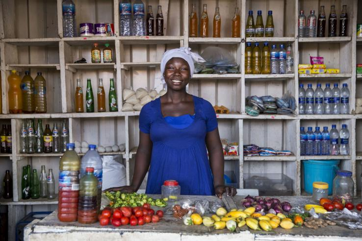 Woman in Ghana stands in front of her roadside restaurant preparing food