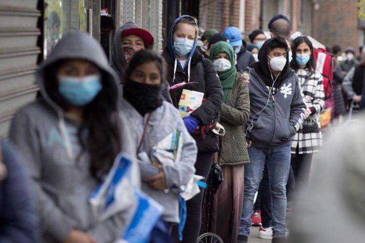 People wearing masks stand in a line.