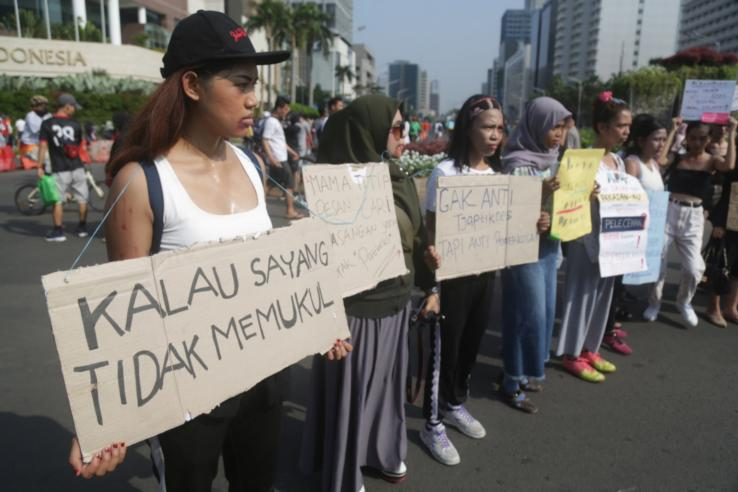 Women holding cardboard signs protesting on a street in Jakarta