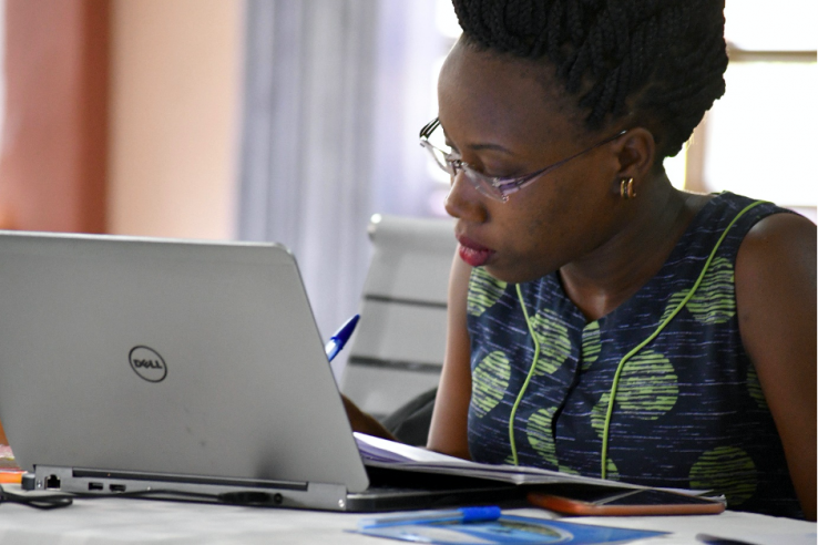 A woman works on her laptop in an office setting in Uganda.