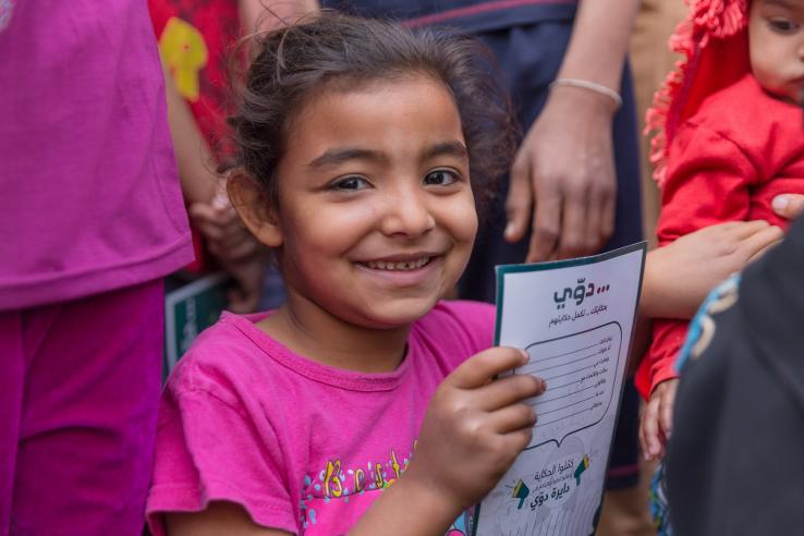 A smiling girl holds a piece of paper.