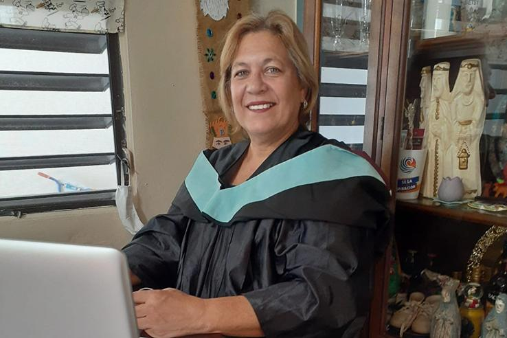 A woman wearing academic dress sits in front of a laptop and smiles at the photographer.