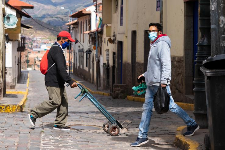 Men walking on the street wearing masks