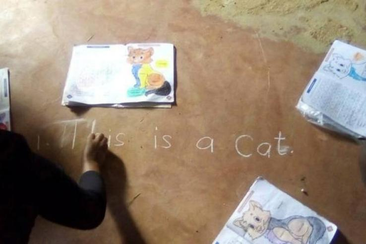 Child sitting on the ground and writing 'this is a cat' on the floor in white chalk
