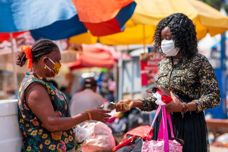 Masked women exchanging money at a market