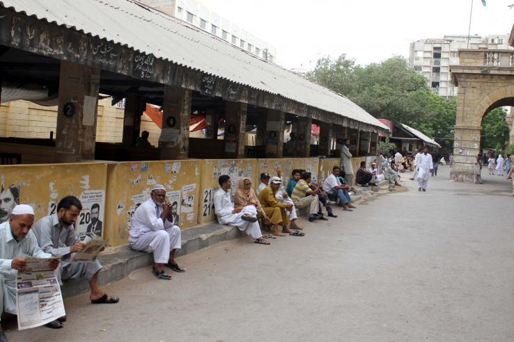 People wait outside a city court in Pakistan