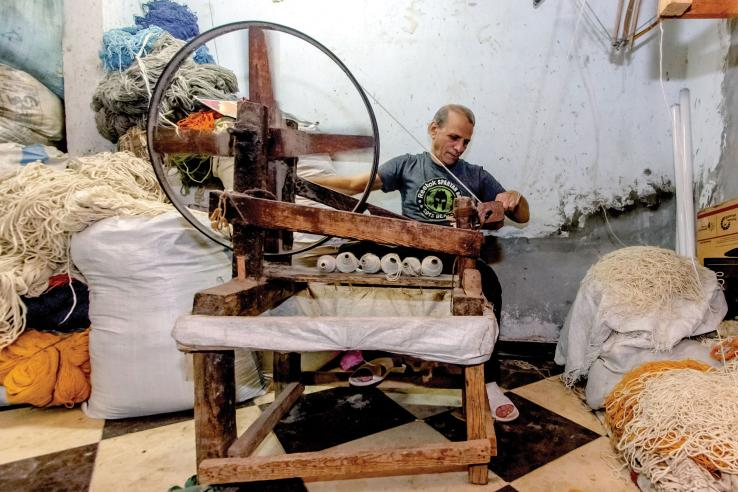 A man weaves a rug. Photo Credit: Haitham Fahmy | J-PAL