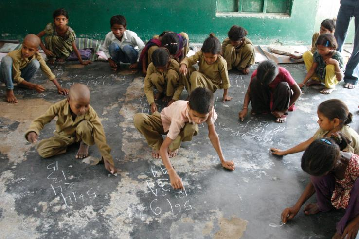 Children do arithmetic in chalk on a stone floor in India