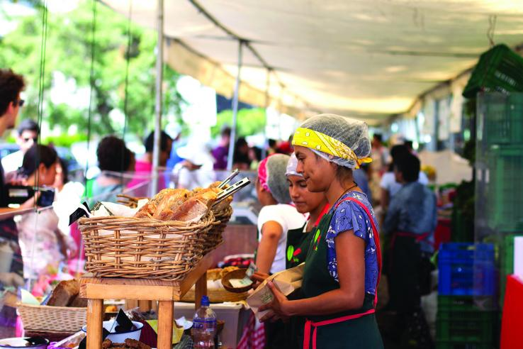 Woman selling bread at a market. Myriam B | Shutterstock