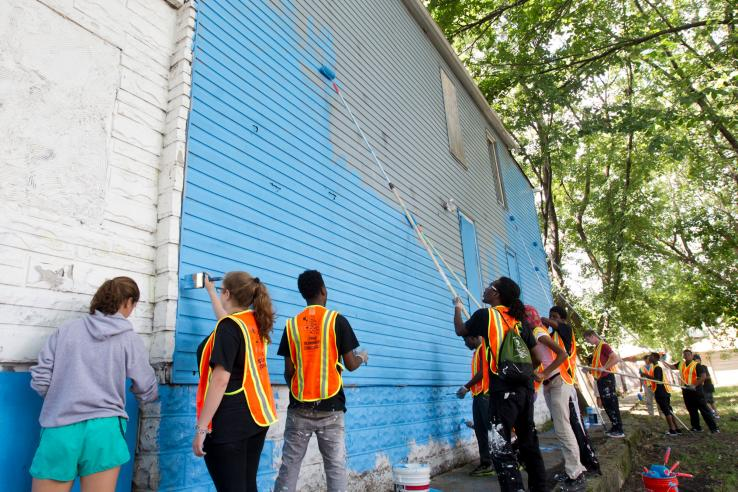 Youth in safety vests painting a wall