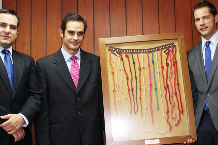 Three men in suits hold framed quipu