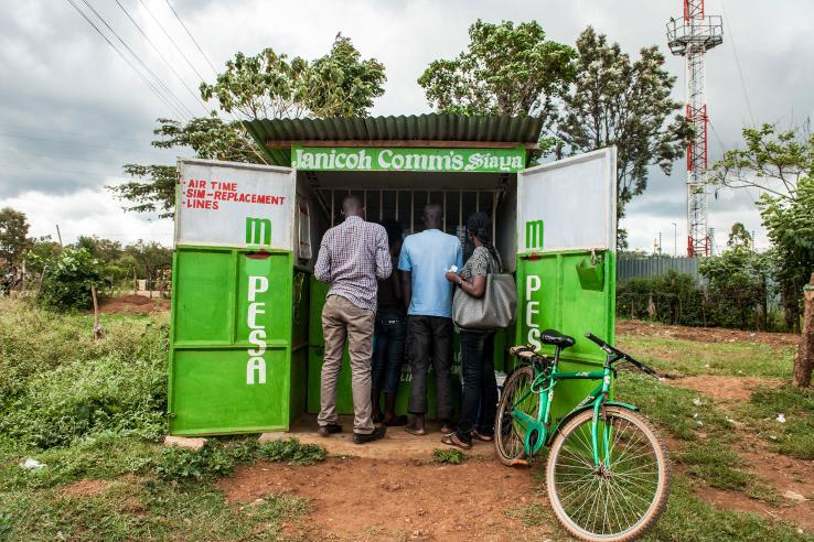 Three people stand at corrugated tin stand advertising mobile services in a field in Kenya
