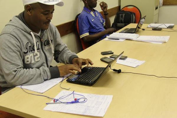 Two enumerators in South Africa conduct phone surveys.