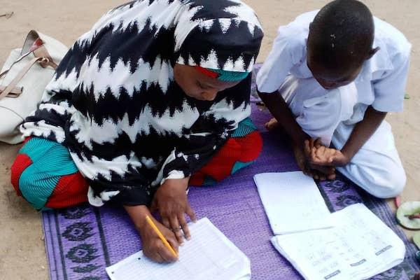 Two children taking an assessment exam on the ground.
