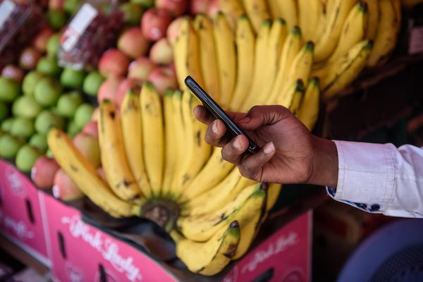 Picture of a person's hand holding a phone in front of a colourful fruit stand.