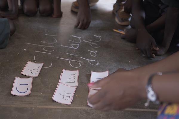 A teacher places phonetics cards on the floor.