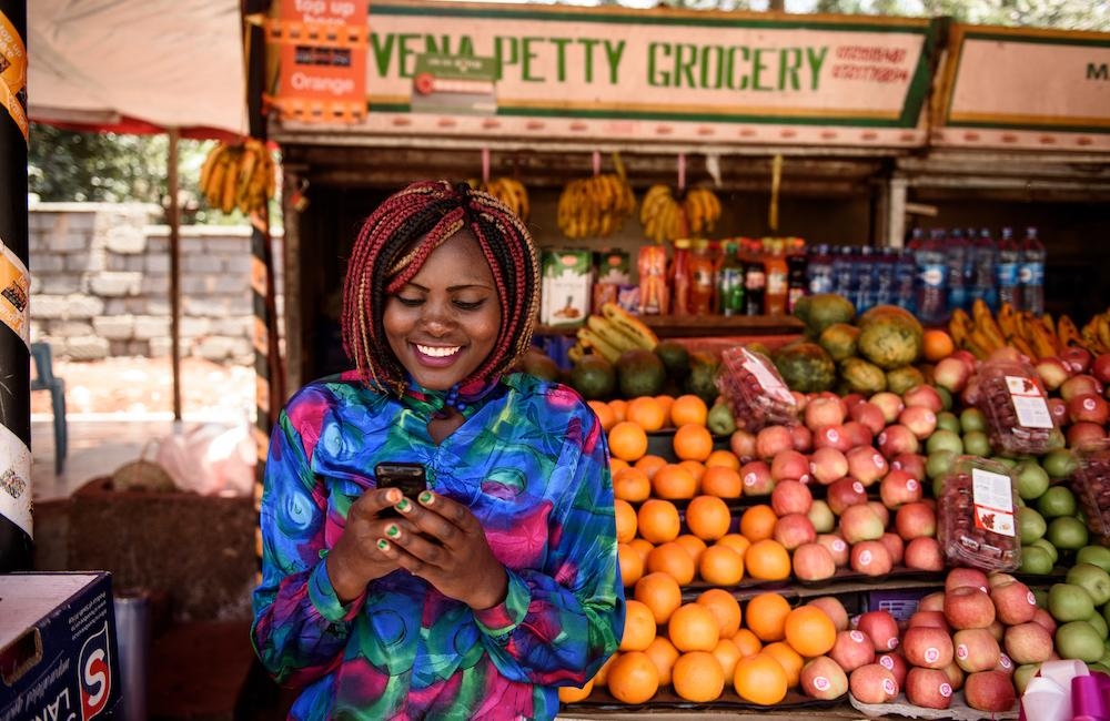 A woman looks at her phone while standing in front of a colourful fruit stand.