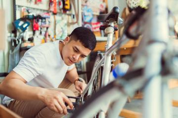 Young man repairing a bike