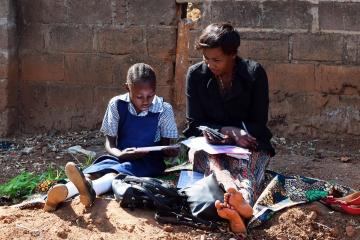 Woman helps a girl with her reading