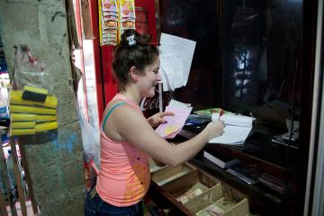 A woman completes paperwork in front of cash register