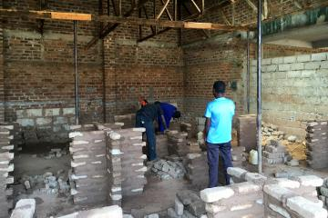 Three young men work on a construction site laying bricks.