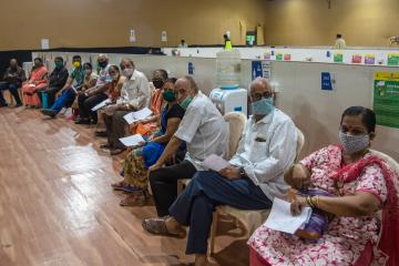 senior citizens wearing masks waiting for the Covid-19 vaccine