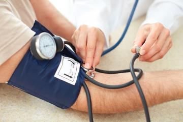 Doctor measures patient's blood pressure