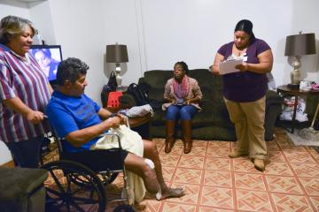Two women with clipboards talk to man in wheelchair in living room
