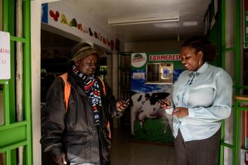 A man and women look at their mobile phones outside a shop in Kenya.