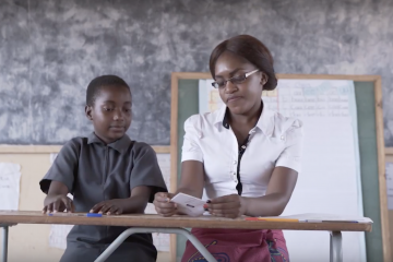 a female teacher and male student in a classroom in Africa