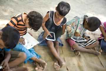 Children sit on the ground, playing on tablets