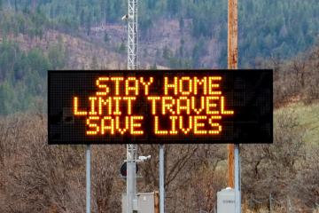"A roadside billboard that reads ""stay home, limit travel, save lives"""